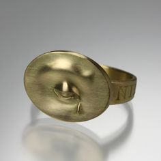 """An 18K yellow gold ring featuring an eye with a  teardrop and an engraving on the band in Latin, """"Nil Nisi Cruce"""", meaning """"nothing without suffering""""  Band tapers from 3-5mm, and placard with eye measures .5mm x .65mm.  Size 7.5."""