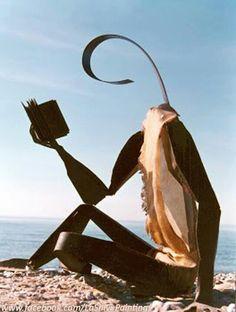 Escultura de lector sentado junto al mar