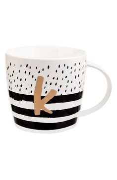 Charming dots and stripes pattern this ceramic mug painted with a single initial monogram.