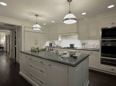 Carole Freehauf Beautiful white kitchen design with white kitchen cabinets, white kitchen island, beveled black granite counter tops, farmhouse sink, sink in kitchen island, Restoration Hardware Clemson Pendants, beveled subway tiles backsplash and coffee stained wood floors.