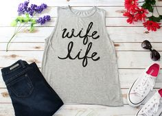 Are you proud to be a wifey? Wear our Wife Life Graphic top loud and proud! Featuring a trendy heather Grey with Black cursive letter across the front, a loose comfy muscle tank style fit, a rounded n