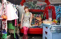 woman selling funky vintage clothing at flea market