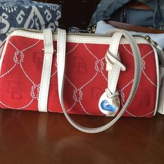 Never used authentic Dooney and Bourke bag Authentic never used Dooney and Bourke bag. Red with logo. Tassel leather zipper. Inside phone holder and clasp for keys. Small Dooney & Bourke Bags Shoulder Bags