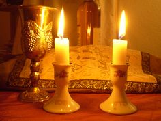 Shabbat candles, challah (covered) and kiddush cup.