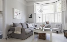 Victorian terrace sitting room, plantation shutters, white wooden floors, grey sofa, light grey walls