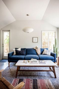 Bright living space with angled ceilings, a saucer pendant light, a midcentury modern blue sofa, and layered rugs
