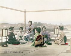 1890's. Geisha Relaxing at Restaurant in Kyoto. Several geisha are relaxing at the Noryo Yuka (納涼床, summer platform) of a restaurant in Kyoto. This photo appears to have been taken at Shijo Ohashi, on the western side of the Kamogawa. The woman in the light kimono is pouring sake, while the two women on the right are playing Jan-ken-pon (known in English as Rock-paper-scissors). Two Andon lamps have been placed on the matted floor.