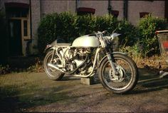 JXD at stage 6, more or less the final version. Notable are: new paint job on tank, fibreglass central oil tank, recovered seat, hot new motor with twin Mk 2 Amals and twin plug heads (both plugs firing on each side due to twin plug coils), alloy headlamp brackets from a post war Norton, and last but certainly not least, that all important chequered tape.