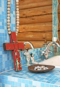 Badet har en frisk kombinasjon av grove tømmervegger og blå mosaikkfliser. Et stort rødt kors, og små menneskefigurer pynter opp på benken. Styling: Tone Kroken.