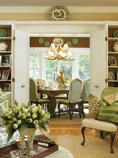 Like the built-in book cases, wooden tray on table, dining room chandelier, plates as decoration.