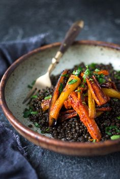 A simple tasty recipe for Roasted Moroccan Carrots- with cumin cinnamon and orange. Serve as a side or over seasoned lentils for a hearty vegetarian meal. | www.feastingathome.com