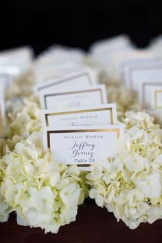 Elegant gold foil-pressed escort cards nestled in hydrangeas. Love this display for a formal wedding! {Photo courtesy of Callawaygable}
