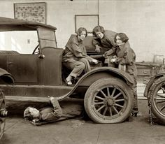 "1927. Central High School, Washington, D.C. ""High school girls learn the art of automobile mechanics. Grace Hurd, Evelyn Harrison and Corinna DiJiulian, with Grace Wagner under the car."" Notice they are ALL BOBBED. If you were driving a car outside a city, you had better know how to do your own repairs!"