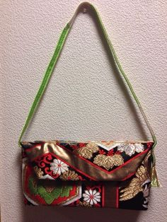 This Kimono Tango Shoulder bag will go perfectly with a formal gown or jeans. This bag features chrysanthemums and tortoise shells, which symbolizes longevity.