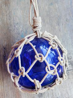 """Beach Decor Cobalt Blue Glass Fishing Float in Rope Netting by SEASTYLE.    (When I was a young girl living on the gulf coast we could pick up these little net covered glass balls that Daddy called """"fishing balls""""...they were like this but a bit different if memory serves me well....however I have pinned it because of that memory of picking them up off the beach when walking there with my dad)."""