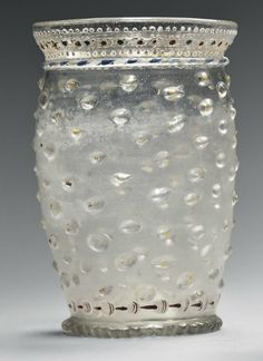 A VENETIAN GLASS ENAMELLED BEAKER   CIRCA 1500   Barrel-shaped with an everted rim, moulded with bands of nodules enriched in gilding, below a thread with blue and white rope-twist and a band of beads and flowerheads in white, blue and red enamels enriched in gilt, the lower part with white and red beads above a milled foot, with a kick-in base