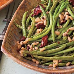 Roasted Green Beans with Sun-dried Tomatoes | Baking your green beans with pine nuts and sun-dried tomatoes is a hands-free way to pack the greens with flavor. | SouthernLiving.com