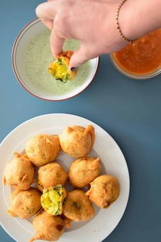 Dipping batata vada into coriander and yoghurt sauce. The ultimate Indian snack food.