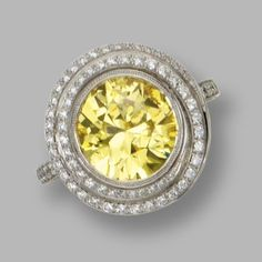 Fancy vivid yellow diamond ring, Chopard. The round diamond of fancy vivid color weighing 4.01 carats, framed by round diamonds weighing approximately .90 carat.
