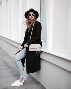 Nina combines ripped denim jeans with white sneakers and a long black overcoat to create an edgy street spring style. She wears these with a wide fedora hat and sunglasses. Brands not specified.