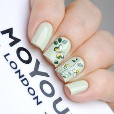 Uñas pintadas con esmalte verde con diseño de flores y mariposas