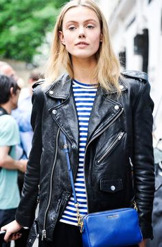 Classic moto jacket in black distressed leather over a nautical blue and white striped crewneck shirt, with bright blue cross body bag, keyed to color of stripes. Uptown grunge :). Style Planet