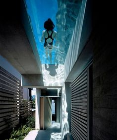 The Shaw House is located on a narrow waterfront property in Vancouver, Canada. The entrance is directly under the pool, midway along the side of the house; an almost magical aqueous light is transmitted to the entrance area through the water and glass bottom of the pool.