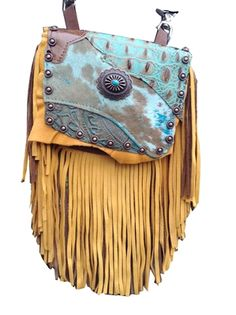 "CARIBBEAN BLUE SANDS MARTY - made of brown deerskin with a 7"" brown & gold deerskin fringe. Flap is acid-treated turquoise hair-on-hide & turquoise printed leather, w/ golden suede backdrop. Centerpiece is an antiqued copper concho w/ flower center, featuring turquoise porcelain. Copper metal studs trim outside, adding a rich tone. Wear bag clipped to belt loops for hands-free carrying of your essentials. Interior includes a leather strap. Add the strap when you want a completely different…"