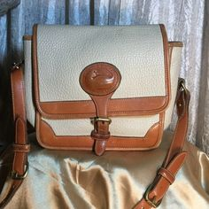 Vintage Dooney+Bourke Here it is girls,  Invest now,  Dooney and Bourke bags will be skyrocketing in price soon.  Forget the mutual  funds you will get a great return on your investment  in these bags.  Light cream color,  outside is clean, strap looks new, inside only a few pen marks Dooney & Bourke Bags Shoulder Bags