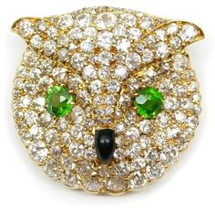 Antique gold, enamel, diamond and demantoid garnet owl's head brooch-pendant by Peacock, American c.1890. The rounded form contoured and pavй set with diamonds, cushion cut demantoid garnet eyes and a black enamel nose, open set in gold, hinged pendant loop to verso.