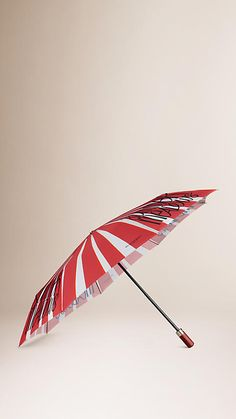 Burberry Pale Rosehip Book Cover Print Folding Umbrella - A folding umbrella featuring an illustrative and typographic print. Inspired by vintage book covers, the artwork is hand-painted in our studio before being printed onto the canopy fabric. The umbrella has a maple wood handle with polished metal detail and a protective case. Discover more accessories at Burberry.com