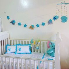 Oh look how cute are these felt elephants marching on a pretty garland above  this baby crib,,,