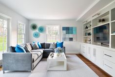 A plush gray sectional is comfortable for the whole family in this fun, contemporary living room. Built-in shelves with lower drawers keep the TV and all other electronics in their place, while blue and gray accents add a relaxing but colorful vibe.