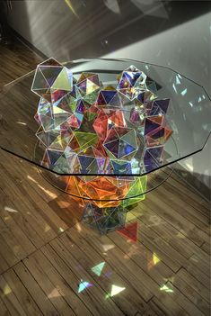 """Minneapolis-based designer John Foster created a magnificent cocktail table, which will make your guests take out their cameras once they enter you living room. His one-of-a-kind """"Sparkle Palace Cocktail Table"""" table is a magnificent fusion of glass and light reflection. A round glass tabletop is placed on a reversed pyramid of elegantly cut glass crystals, which divide the natural light into hundreds of rainbow reflections the walls."""