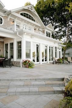 I like the idea of the large porch area, i would have it raised with the stone and then down the steps would be large area of grass