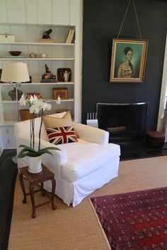 antique oriental rug over sisal rug with a Union Jack pillow on a slipcovered chair