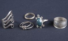 MISCELLANEOUS LOT OF VINTAGE TO NEWER STERLING SILVER RINGS INCLUDES A TAXCO RING WITH ADJUSTABLE BAND AND CURLED EXTENSIONS, A TURTLE WITH STONE CABOCHON, TWO STERLING BANDS AND A DOUBLE RING WITH LOVERS KNOT. ALL IN GOOD CONDITION.
