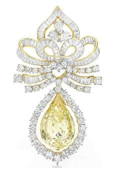 A COLORED DIAMOND BROOCH. Suspending a fancy yellow briolette-cut diamond, weighing approximately 60.81 carats, swinging within a circular-cut diamond frame, to the circular-cut and baguette-cut diamond openwork plaque, mounted in 18k yellow and white gold.