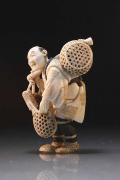 Antique Japanese incised and delicately carved netsuke figure; of a basket vendor carrying his wares hung on a bamboo pole over his shoulder, artist's signature to the base, early 20th Century era. Size; Height of carving is 2 inches.