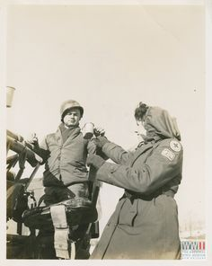 """Photograph. """"2 Jan 1945. 5/MM-45-153. Fifth Army, Loiano Area, Italy. Lee Harris, Butte, Mont. [Montana] of the American Red Cross, giving hot coffee to PFC. Joe Bergles, Pueblo, Colo. [Colorado], 105th A.A. Battalion. Photo by Schmidt. 3131 Signal Service Co."""" Loiano Area, Italy. 2 January 1945"""