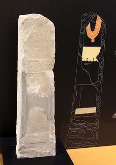 Sala V. El mundo funerario y religioso. Estela hallada en La Serrada (Ares del Maestre, Castellón) fechada entre los siglos IV-III a.C. que no ha conservado la cabeza. Representa un personaje femenino que ostenta joyas (tres collares y cinturón con colgantes)  y una cuidada indumentaria que se identifica por la cenefa decorativa en la parte inferior de la túnica.