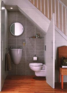 unique miniature bathroom under the stairs, clever use of space // might feel a little silly using it, though... prolly feels like using an airplane bathroom!