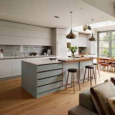 Kitchens: Modern Kitchen with Handleless Cabinetry also Metallic Pendant Light plus Hardwood Flooring and Glass Countertop