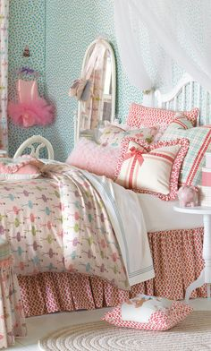 Little girls ballerina bedroom. The bed has a white wooden frame. The sheets have pastel coulors. There are many different sizes pillows.