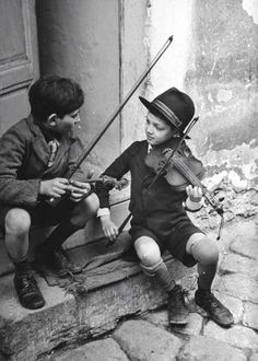 Gypsy children playing violins in the street, Budapest, Hungary, 1939