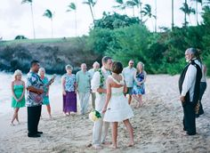 24-bridal-couple-kissing-ceremony-guests-standing-beach-musician-officiant-strapless-dress-lei