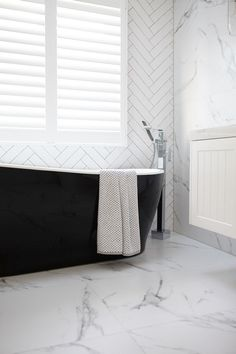 Bathroom with black tub and white marble floors #marblebathrooms