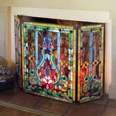 """$269.95 STAINED GLASS FIRESCREEN: Handcrafted and soldered with 541 pieces of art glass, the fleur de lis motif is magnificently realized in our three panel design with hinged metal frames. Position at least 12"""" away from front of the fireplace, or fill your fireplace with candles and watch it glow. Center is 22""""W; the sides are 11""""W x 28""""H."""