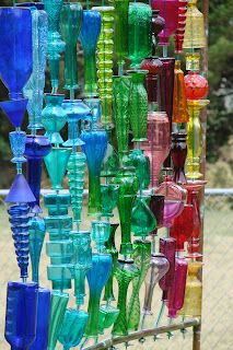 This bottle wall yard art is made out of bottles found at yard sales, Goodwill, flea markets, etc. It's so beautiful in all kinds of light. #upcycle