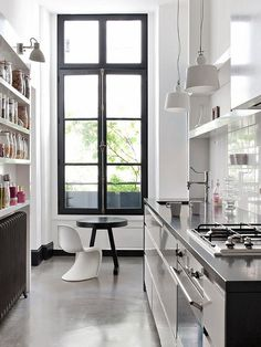 Urban Galley Kitchen with tall black metal framed window and polishe concrete floors| Remodelista